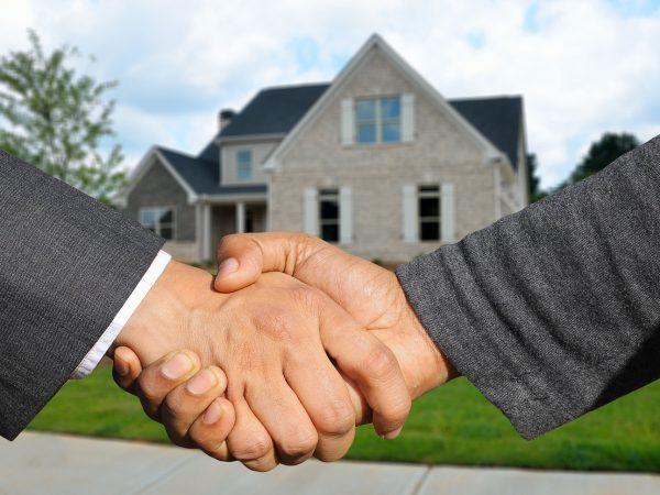 personnes se serrant la main devant une maison après promesse de vente
