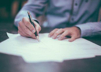homme signant un contrat contenant une clause de garantie d'actif et de passif (GAP)
